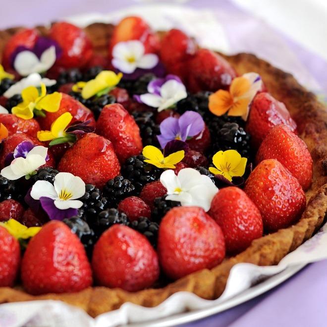 Aardbeien-bramentaart met eetbare bloemen.